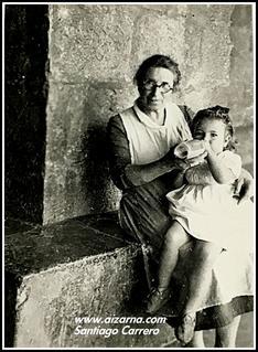 Zz-Margarita Egiguren  Bastida dando el biberón  en el pórtico de la Iglesia año 1945 Margarita Eguiguren haur txiki bat  besoetan duela 1945 urtean